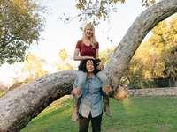 nő szürke ujjatlan ruhában állt barna fa mellett