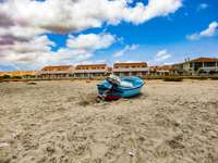 blue and white boat on brown sand under blue sky