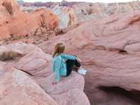 woman in blue jacket sitting on brown rock formation