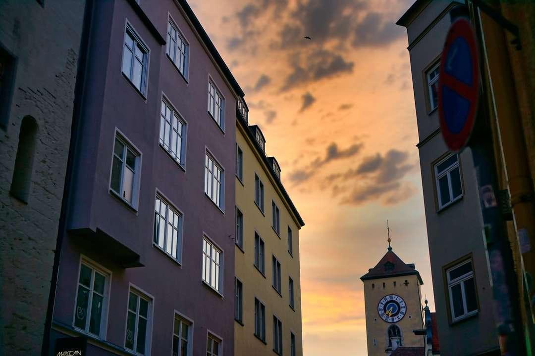 Bâtiment en béton gris avec tour de l'horloge sous un ciel nuageux