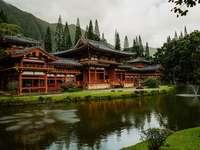 кафяв и черен храм близо до езеро и зелени дървета