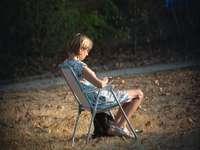момче в син потник, седнало на сгъваем стол