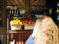 osoba v modré džínové džíny stojící poblíž stánek s ovocem