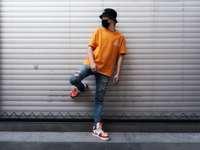 bărbat în tricou portocaliu cu guler echipat și blugi din denim albastru