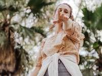 nő barna kötött pulóverben és szürke farmerben