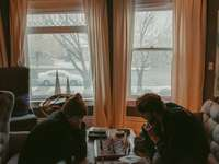 2 жени, седнали на стол близо до прозореца