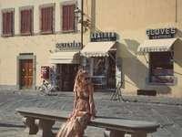 жена в кафява рокля, седнала на пейка близо до сградата