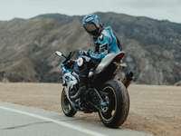 mężczyzna w niebiesko-białej kurtce na czarnym motocyklu