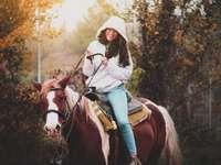kvinna i vit långärmad skjorta som rider brun häst