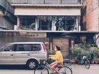 man in yellow shirt riding bicycle near black car