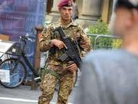 мъж в зелена и кафява камуфлажна униформа, държащ пушка