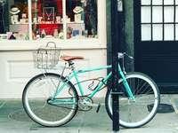 turkusowy rower miejski zaparkowany obok sklepu