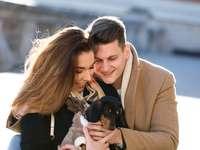 Mujer en abrigo marrón abrazando perro salchicha negro y marrón