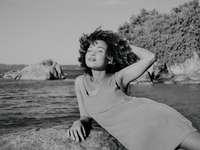 donna in canottiera seduta sulla roccia vicino al corpo d'acqua