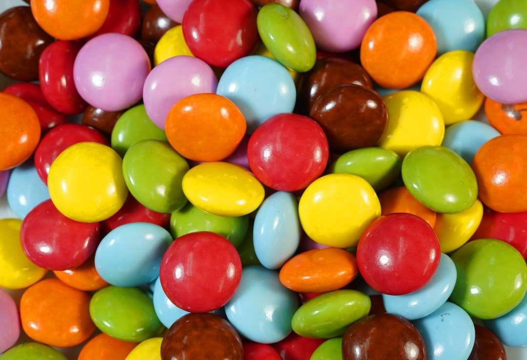 różne kolorowe cukierki na brązowym drewnianym stole