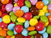 разнообразни цветни бонбони върху кафява дървена маса