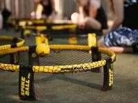 bola de tênis amarela em cama elástica preta e amarela
