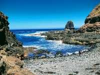 brown rocky mountain beside sea under blue sky