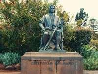 Hombre en estatua de túnica cerca de plantas verdes durante el día