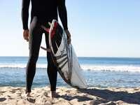 Persona con tabla de surf blanca y azul de pie en la playa