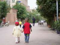 boy in red and blue shirt and gray pants holding girl