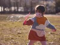 garota de vestido branco e vermelho jogando bolhas durante o dia