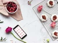 iphone 5 c negru și roșu lângă cana ceramică albă