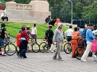 lidé jedoucí na kole na šedé betonové silnici během dne