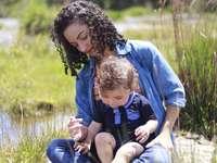 жена в синя и зелена качулка, носеща дете в синя качулка