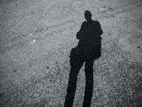 Sombra de la persona en la carretera de asfalto gris durante el día