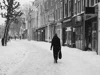 човек в черно палто, ходещ по заснежен път