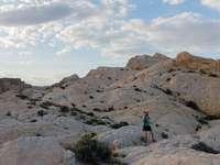 άτομο με μπλε σακάκι στέκεται πάνω σε βραχώδη λόφο κατά τη διάρκεια της ημέρας