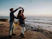 man en vrouw staan overdag op het strand