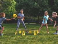 2 kobiety grające w piłkę nożną na zielonej trawie w ciągu dnia