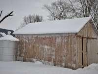 кафява дървена къща, покрита със сняг