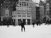 oameni care merg pe câmp acoperit de zăpadă lângă clădire