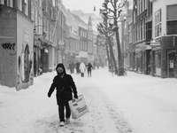 жена в черно палто, носещо бяла найлонова торбичка