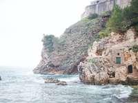 brun betongbyggnad på klippan vid havet under dagtid