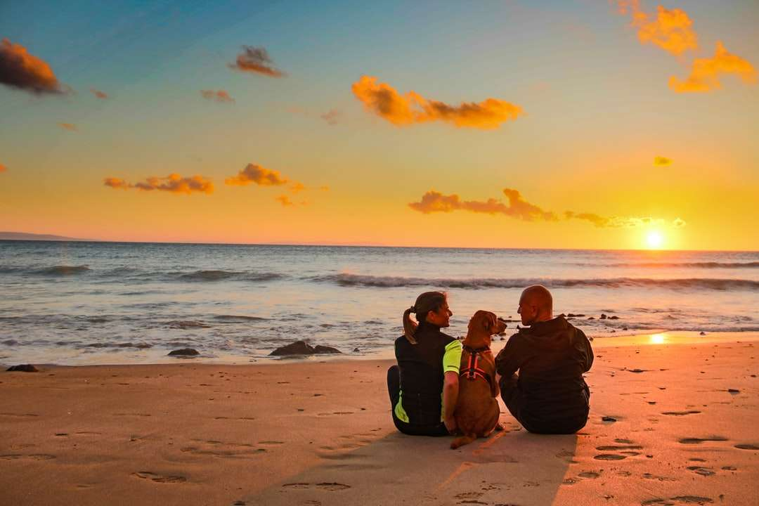 man and woman sitting on beach during sunset