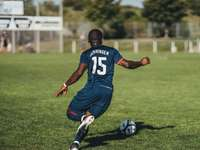 Mann im blauen und weißen Trikothemd, das Fußball spielt