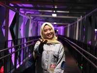 žena v modré džínové bundě stojící na mostě