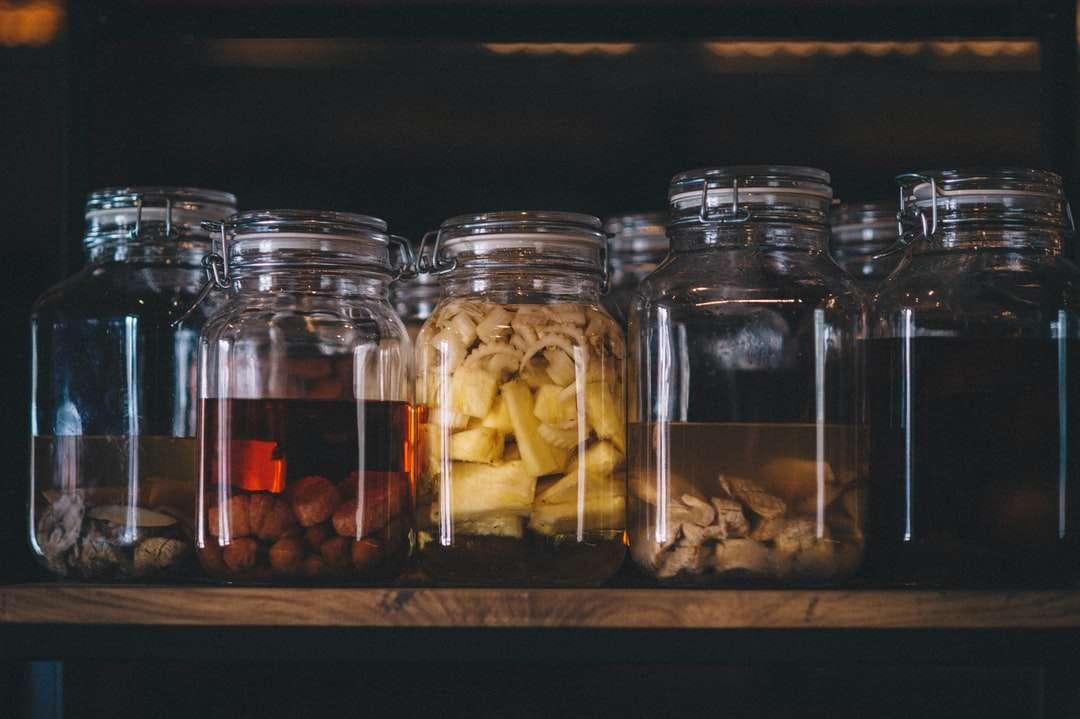 barattoli di vetro trasparente con pietre marroni e bianche