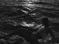 nő ül a vízen fehér inget