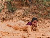мъж в розова риза, лежащ върху кафяв пясък през деня
