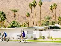 homem de camisa azul andando de bicicleta na estrada durante o dia
