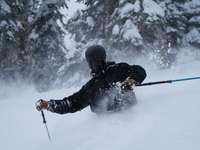 мъж в черно яке и черен панталон, каращ ски остриета