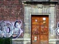 hnědé dřevěné dveře s bílými a modrými graffiti