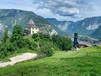 edificio in cemento bianco vicino ad alberi verdi e montagne