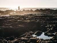 άτομο που στέκεται πάνω σε σχηματισμό βράχου μπροστά από το νερό του ωκεανού