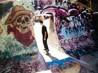 fekete ingben és nadrágban a fal mellett álló férfi